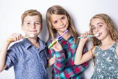 Tre lilla childs som borstar tänder som isoleras på vit Royaltyfri Bild