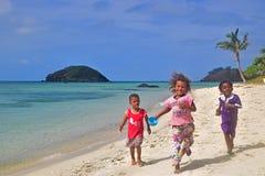 Tre lilla Fijianungar från Yasawa öar som kör in mot kameran royaltyfria foton