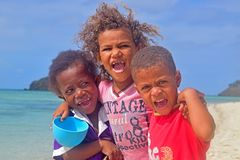 Tre lilla Fijianungar från Yasawa öar som ler med mycket spänning som klart är synlig från deras franka skri av glädje royaltyfri fotografi