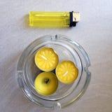 Tre lilla gula aromatiska stearinljus med en gul tändare Arkivbild