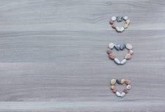 Tre lilla hjärtor av mångfärgade kiselstenar på träyttersida lodisar Arkivfoto