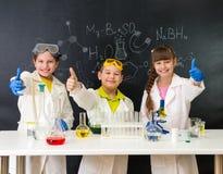 Tre lilla studenter på kemikurs i labb Arkivbild