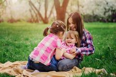 Tre lilla systrar som har mycket gyckel som tillsammans spelar utomhus- i sommar, parkerar på semester Fotografering för Bildbyråer