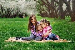 Tre lilla systrar som har mycket gyckel som tillsammans spelar utomhus- i sommar, parkerar på semester Royaltyfria Bilder