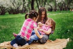 Tre lilla systrar som har mycket gyckel som tillsammans spelar utomhus- i sommar, parkerar på semester Royaltyfri Fotografi
