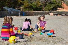 Tre lilla systrar som spelar i sanden på stranden Arkivbild