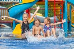 Tre lilla ungar som spelar i simbassängen Arkivbild