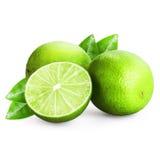 Tre limefrukter som skivas på vit Arkivbild