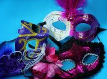 Tre ljusa karnevalmaskeringar på en blå bakgrundsnärbild Royaltyfri Fotografi