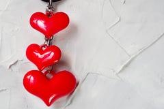 Tre ljusa röda hjärtor på grånar konkret bakgrund royaltyfria foton