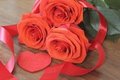 Tre ljusa röda rosor, teckenhjärta och satängband på träbakgrundscloseupen Royaltyfri Foto