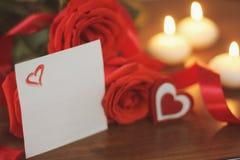 Tre ljusa röda rosor, teckenhjärta, satängband, ark av papper och bränningstearinljus på träbakgrundscloseupen Royaltyfri Bild