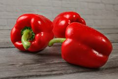 Tre ljusa röda spanska peppar på träskrivbordet, fokus som bevattnar dro arkivbilder