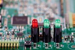 Tre ljusdioder i håligheter på ett strömkretsbräde Arkivbild