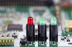 Tre ljusdioder i håligheter på ett strömkretsbräde Arkivfoto