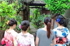 Tre lokala japanska unga kvinnor som bär typisk kläder och en europeisk turist, går tillsammans till och med en japansk typisk tr royaltyfri bild