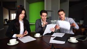 Tre lyckade chefer, två grabbar och flickan förbereder åsikt på giltighet av försäkringbetalningar, bruksgrejer och att se arkivfilmer