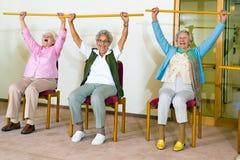 Tre lyckliga äldre damer som gör övningar Royaltyfri Bild