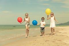 Tre lyckliga barn med ballonger som kör på stranden på Det Royaltyfri Fotografi