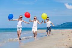 Tre lyckliga barn med ballonger som kör på stranden på Det Royaltyfri Foto