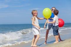 Tre lyckliga barn med ballonger som spelar på stranden på Royaltyfri Fotografi