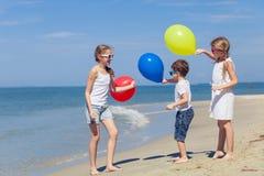 Tre lyckliga barn med ballonger som spelar på stranden på Arkivfoto