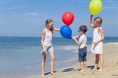Tre lyckliga barn med ballonger som spelar på stranden på Fotografering för Bildbyråer