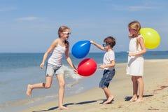 Tre lyckliga barn med ballonger som spelar på stranden på Det Royaltyfri Foto