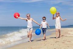 Tre lyckliga barn med ballonger som spelar på stranden på Det Arkivbild