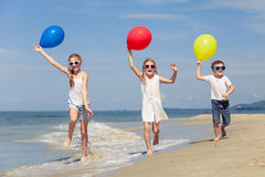 Tre lyckliga barn med ballonger som spelar på stranden på Det Royaltyfria Bilder
