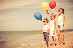 Tre lyckliga barn med ballonger som står på stranden på Royaltyfri Fotografi