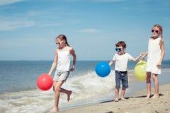 Tre lyckliga barn med ballonger som står på stranden på Royaltyfri Bild