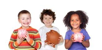Tre lyckliga barn med spargrisar Arkivbild