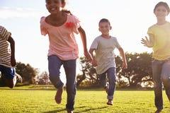 Tre lyckliga barn som barfota kör i ett fält i sommar arkivfoto