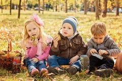 Tre lyckliga barn som spelar i höst, parkerar med frukter Arkivbild