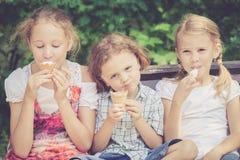 Tre lyckliga barn som spelar i parkera på dagtiden Arkivfoton
