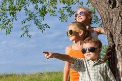 Tre lyckliga barn som spelar i parkera på dagtiden Royaltyfria Bilder