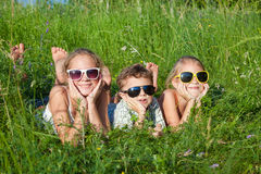 Tre lyckliga barn som spelar i parkera på dagtiden Royaltyfri Bild