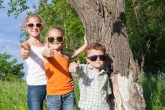 Tre lyckliga barn som spelar i parkera på dagtiden Arkivbilder