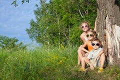 Tre lyckliga barn som spelar i parkera på dagtiden Royaltyfria Foton