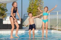Tre lyckliga barn som spelar på simbassängen på dagen tim Fotografering för Bildbyråer