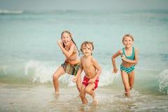 Tre lyckliga barn som spelar på stranden arkivfoton