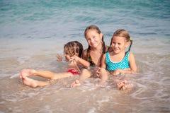 Tre lyckliga barn som spelar på stranden Arkivbild