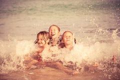 Tre lyckliga barn som spelar på stranden Royaltyfria Bilder