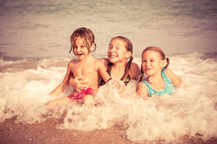 Tre lyckliga barn som spelar på stranden Royaltyfria Foton