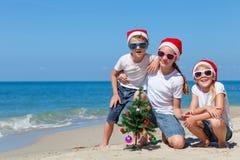 Tre lyckliga barn som spelar på stranden på dagtiden Royaltyfri Foto