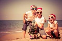 Tre lyckliga barn som spelar på stranden på dagtiden Arkivfoto