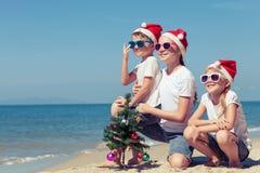 Tre lyckliga barn som spelar på stranden på dagtiden Royaltyfri Bild