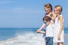 Tre lyckliga barn som står på stranden på dagtiden Royaltyfri Bild