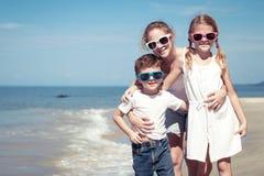 Tre lyckliga barn som står på stranden på dagtiden Royaltyfri Foto